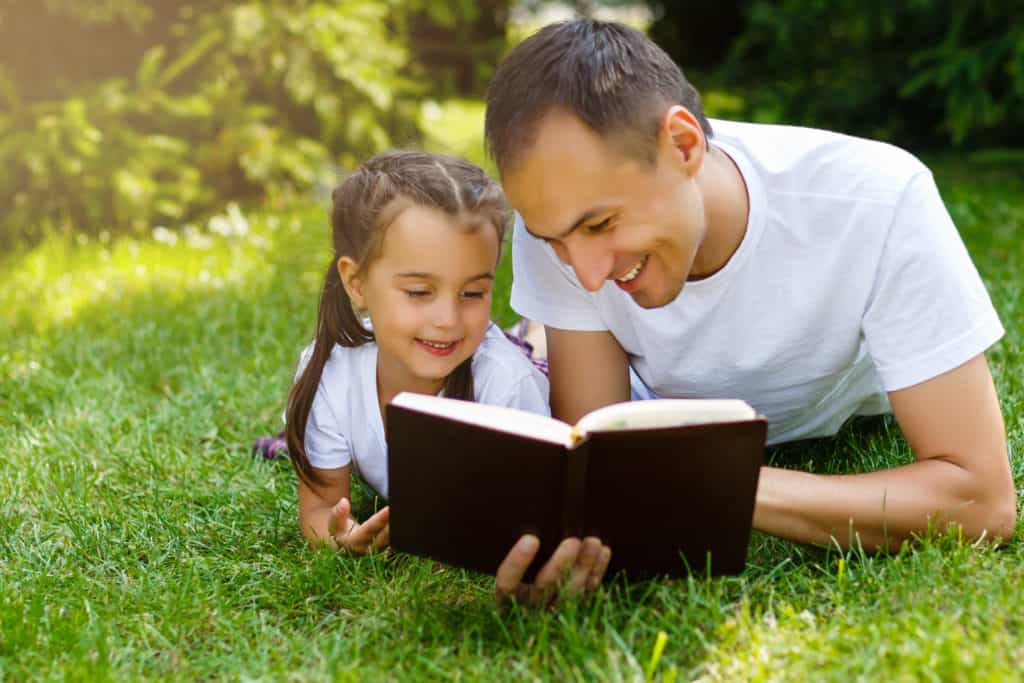 Father and daughter read Bible outdoors