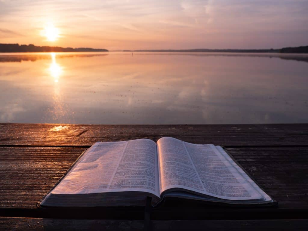 open bible on dock overlooking sunset