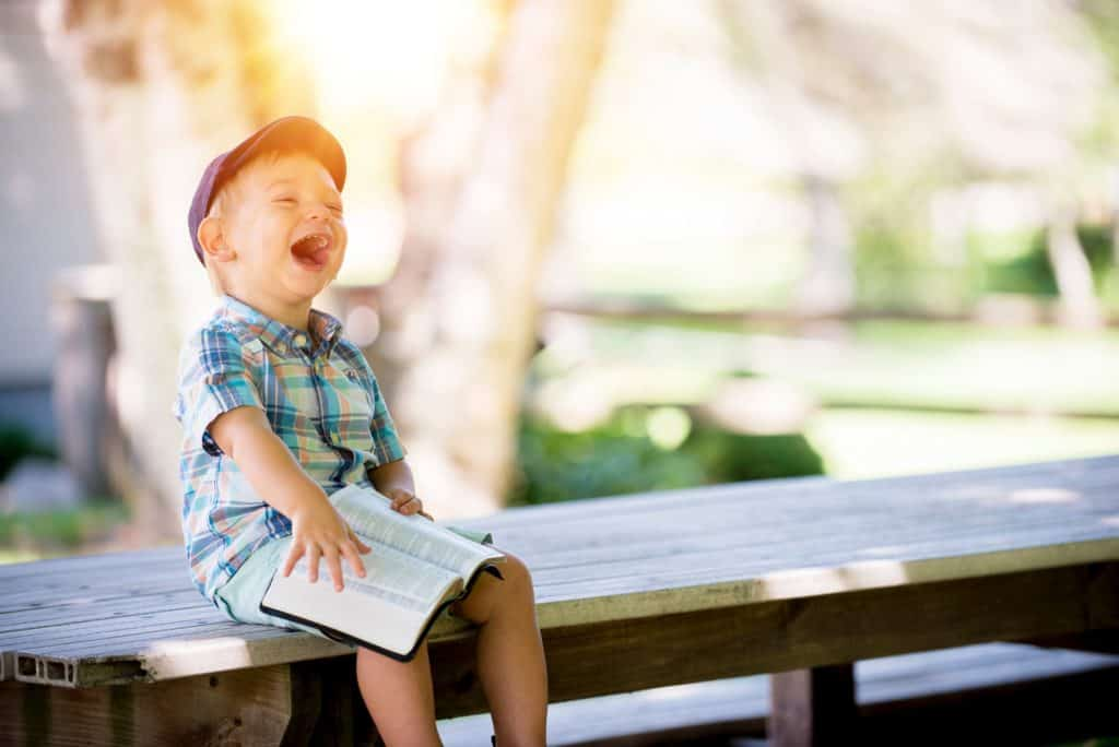 little boy in blue hat on bench laughing with open bible on lap