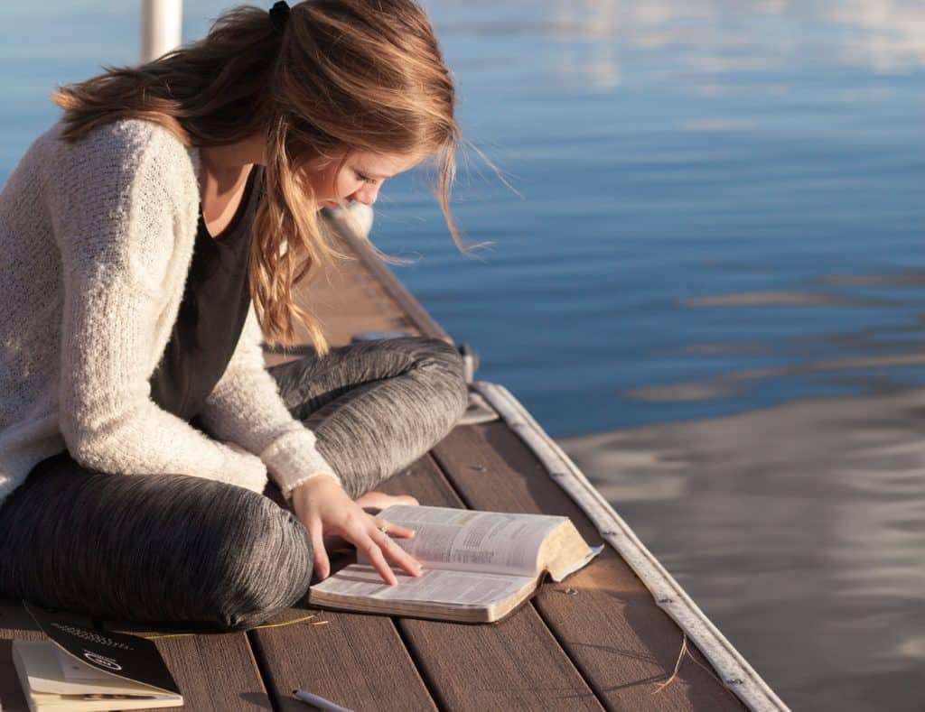 Young woman reading Bible on a dock