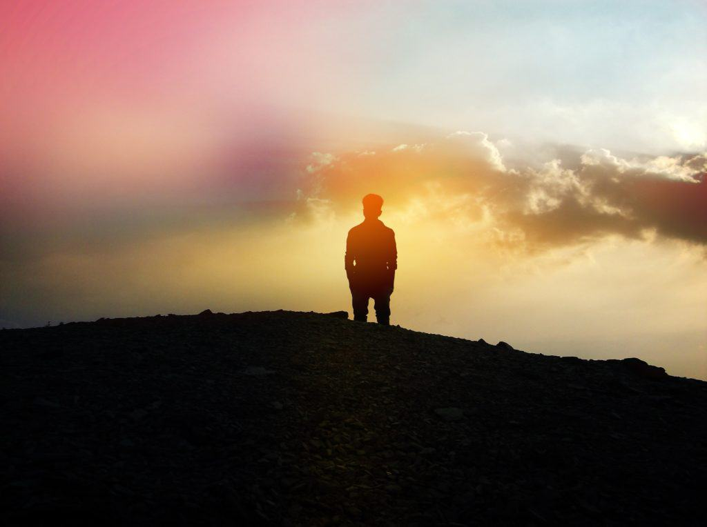 Man on hill with colorful sky in background