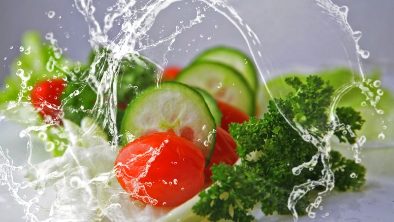 cucumbers, tomatoes, parsley, and lettuce with large splashes of water surrounding them