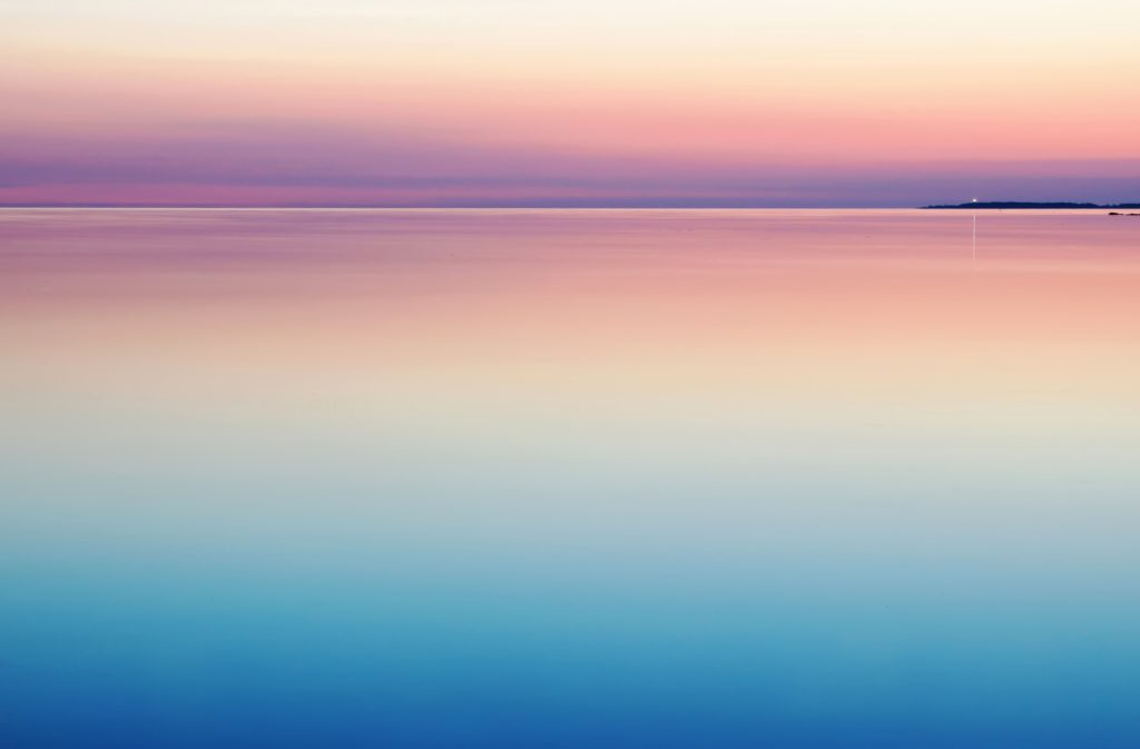blue and pink sunset on calm lake