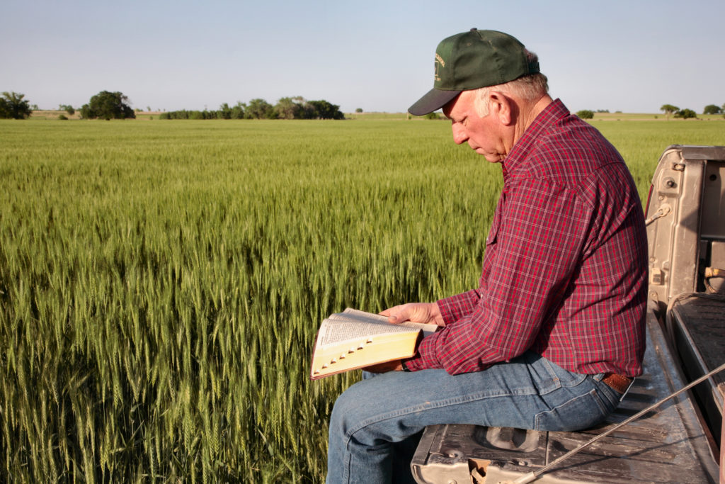 Farmer reading Bible while sitting on truck tailgate