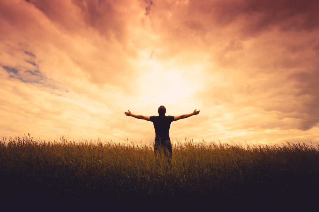 Man standing in field with outstretched arms looking up to heaven