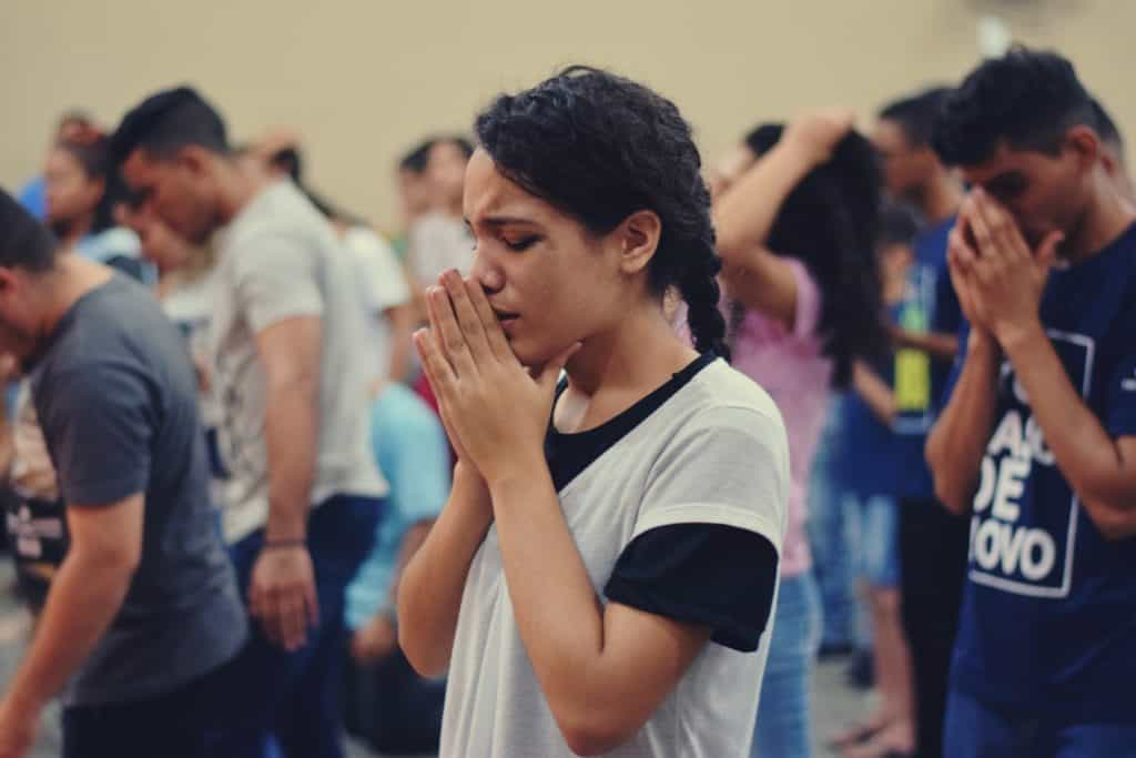 Young woman praying in group of people