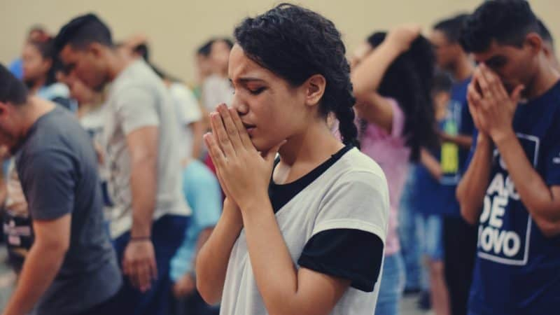 group of youth earnestly in prayer before having a Bible study