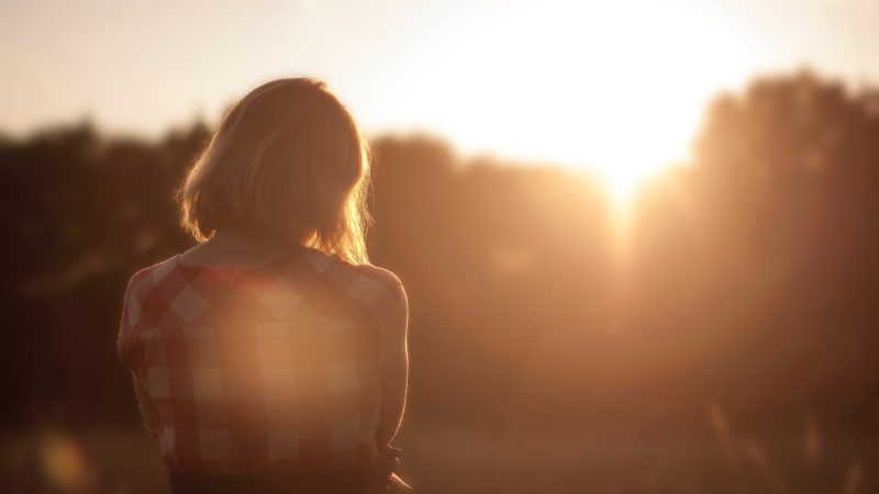 woman standing in field at sunset saying a prayer for God to change her heart