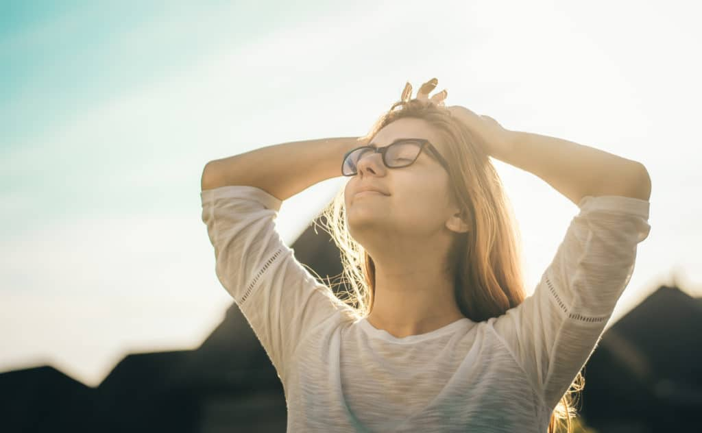 young woman with glasses taking in sunshine from heaven