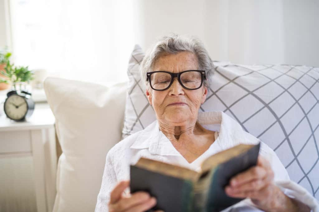 older woman lying in bed reading bible