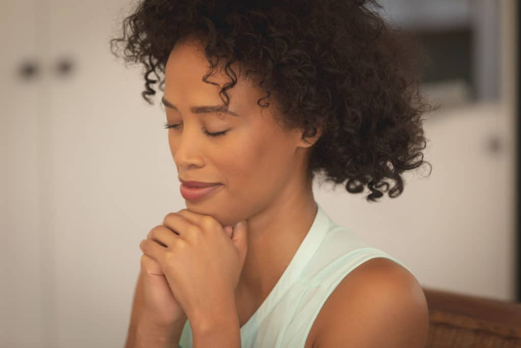 Woman praying with eyes closed and hands clasped