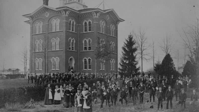 black and white large 3 story house with many adventist members standing in the front yard