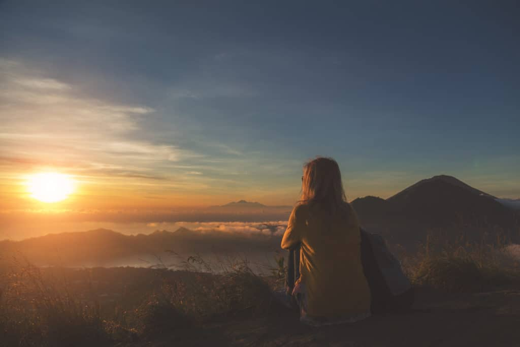 Woman outdoors with sun low on horizon