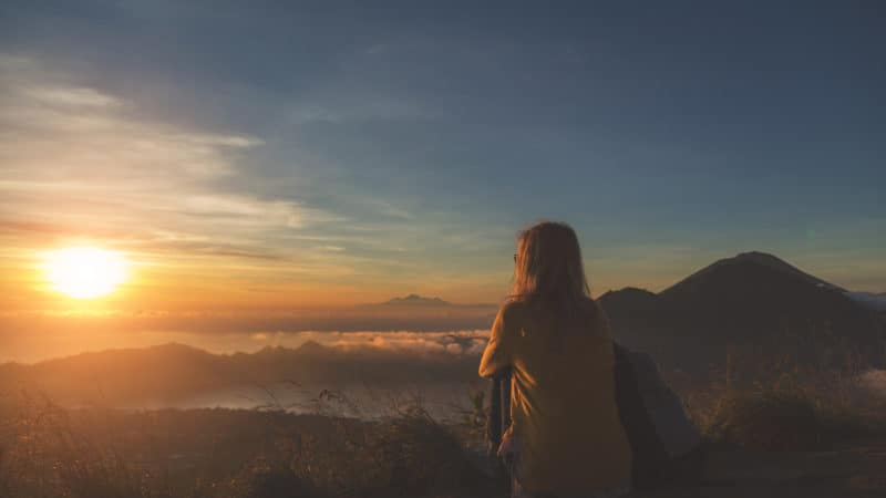 woman sitting on top of a mountain overlooking a valley at sunset and feeling close to God