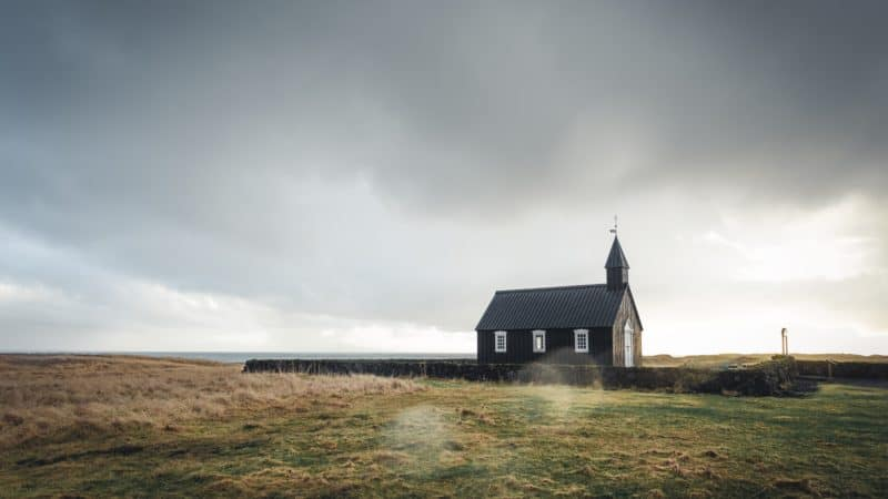 small brown church alone in a field surrounded by a hedge