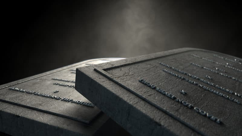 two grey stone tablets with the ten commandments written on them and leaning against each other horizontally