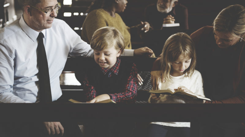 Family sitting together in church pew on Sabbath reading the Bible