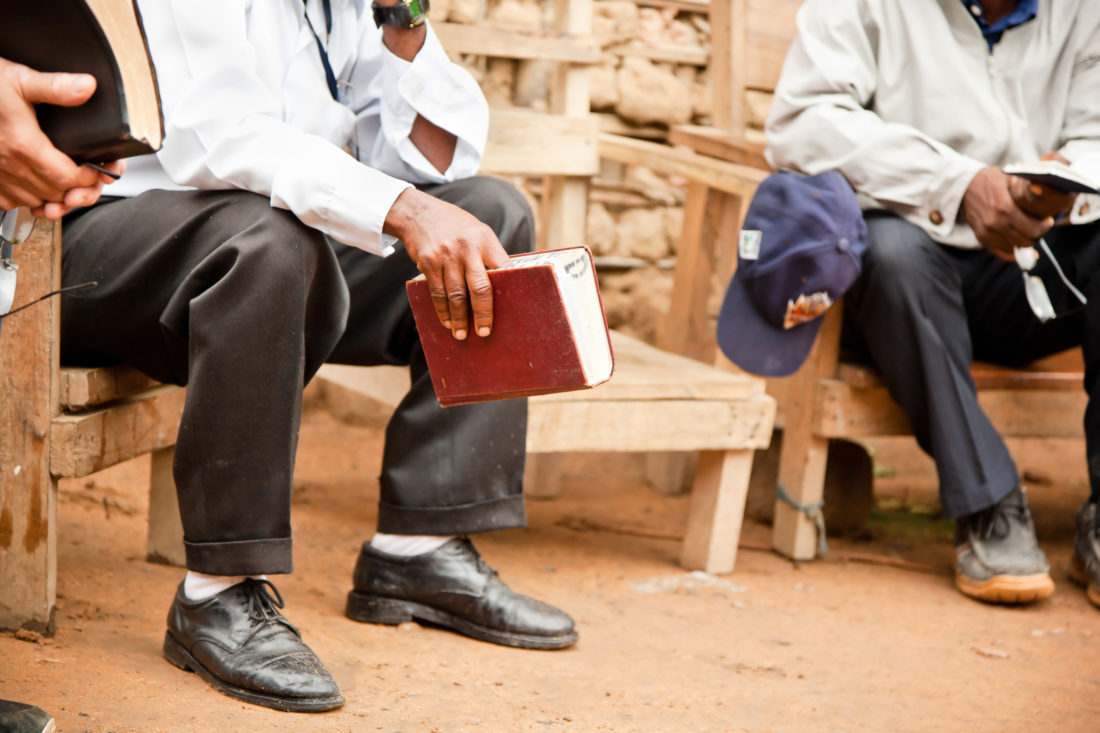 Men sitting outdoors with Bibles