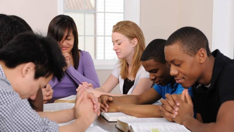 Bible study group praying together
