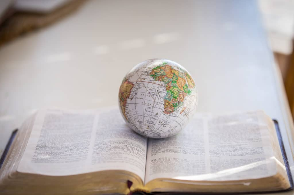 Small globe sitting on open Bible