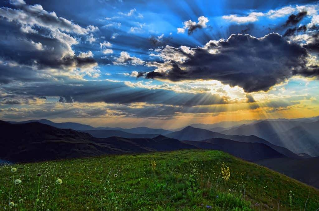 sun beams shining through clouds in heavens over alpine meadow