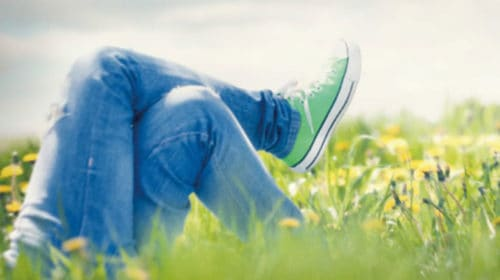 boy relaxing in a field of green grass enjoying the Sabbath rest talked about in scripture