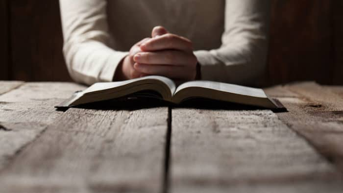 Man with bible open on a table folding his hands and praying
