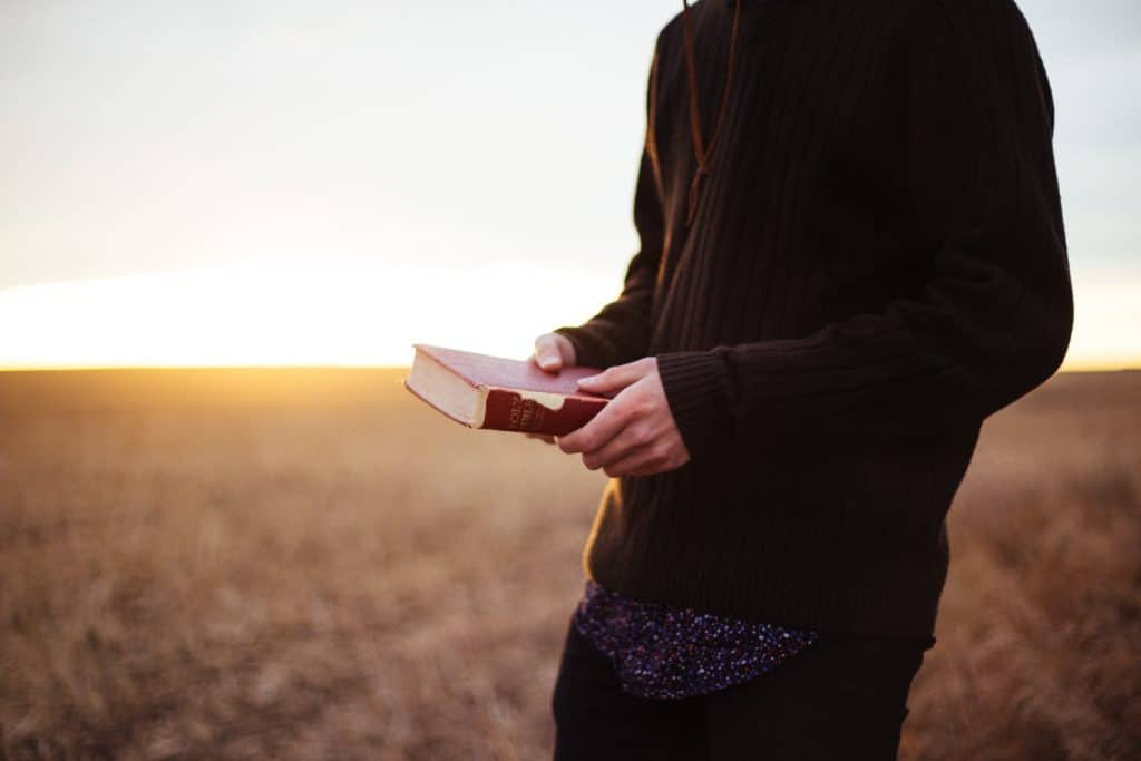 Man holding a Bible in a field at sunset