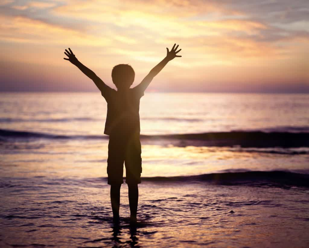 Silhouette of a boy with hands raised in the sunset over the sea
