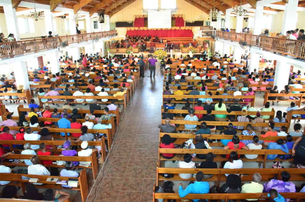 A church filled with congregants sitting in the pews.