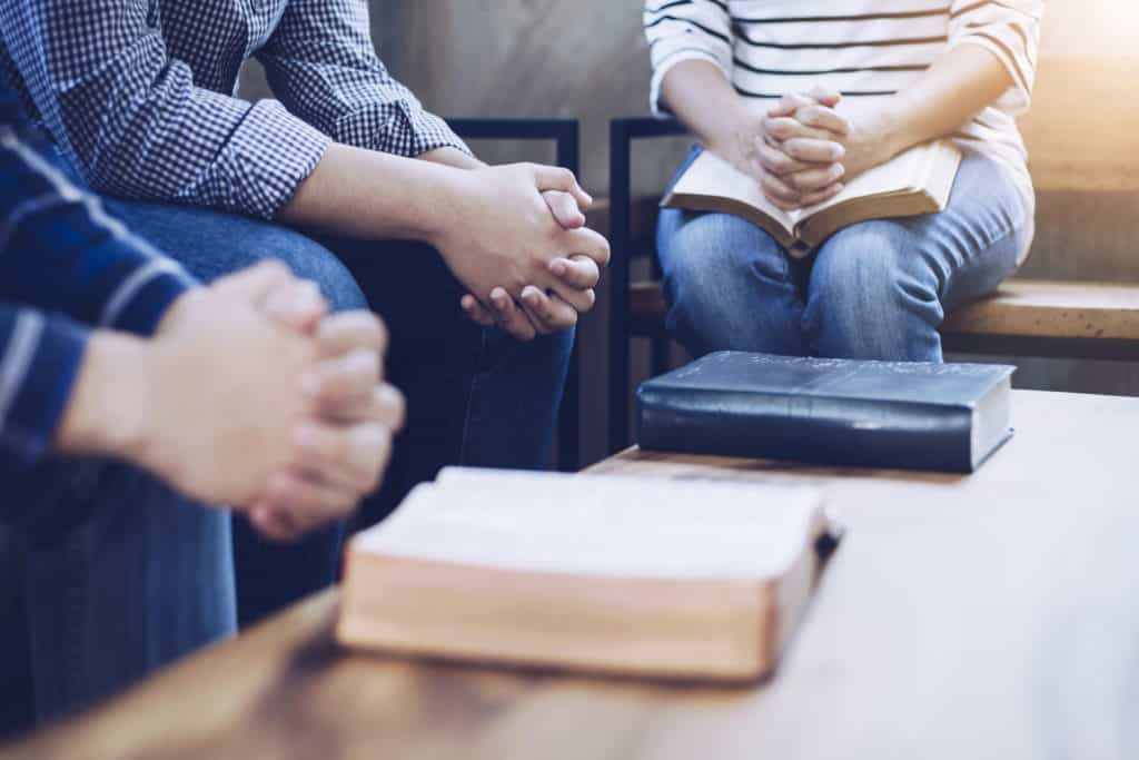 Christian group are praying together around wooden table with holy bible
