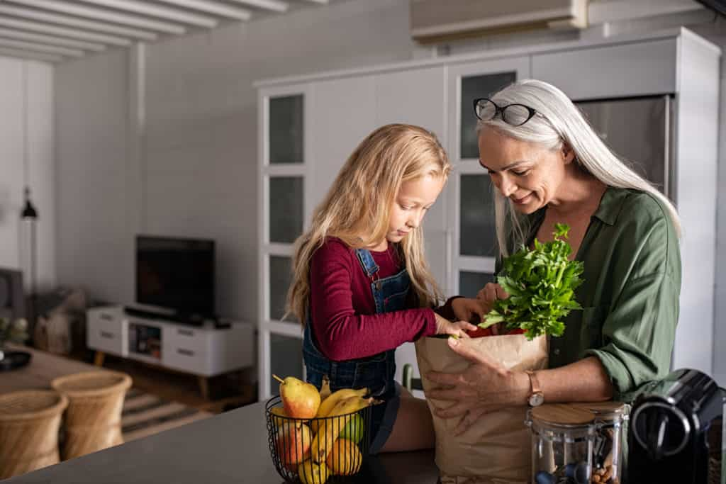 Grandmother and her granddaughter holding grocery shopping bag with vegetables at home.