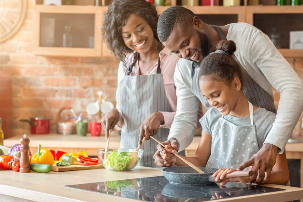 Kind afro parents teaching their adorable daughter how to cook healthy food in kitchen.
