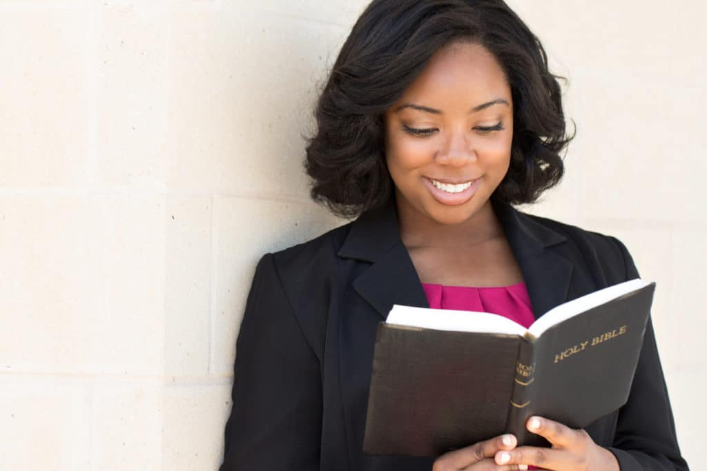 Well dressed African American woman reading her  Bible