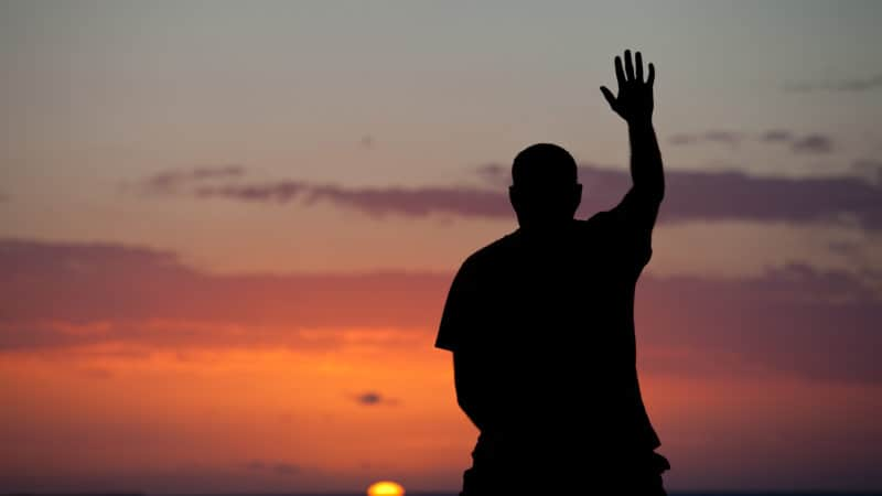 Silhouette of a man lifting his hand towards heaven as the sun sets on the ocean.