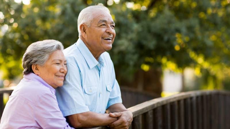 A senior couple enjoy their afternoon on a bridge.