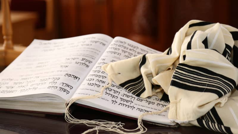 black and white Jewish prayer shawl draped over open bible written in Hebrew text symbolizing the sabbath throughout history