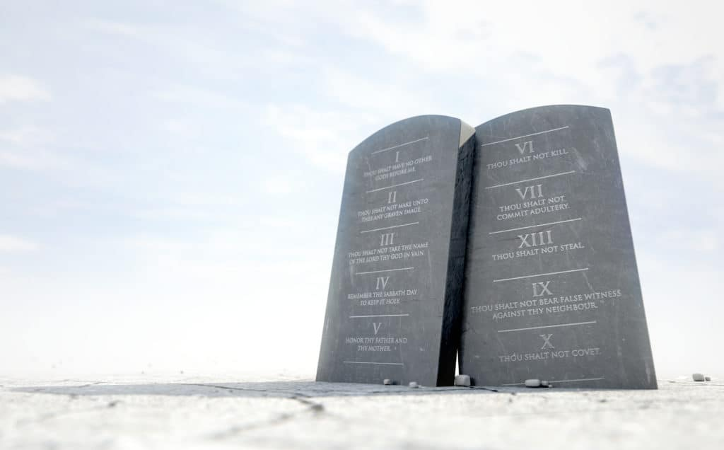 Two stone tablets with the ten commandments inscribed on them standing in brown desert sand in front of a blue sky