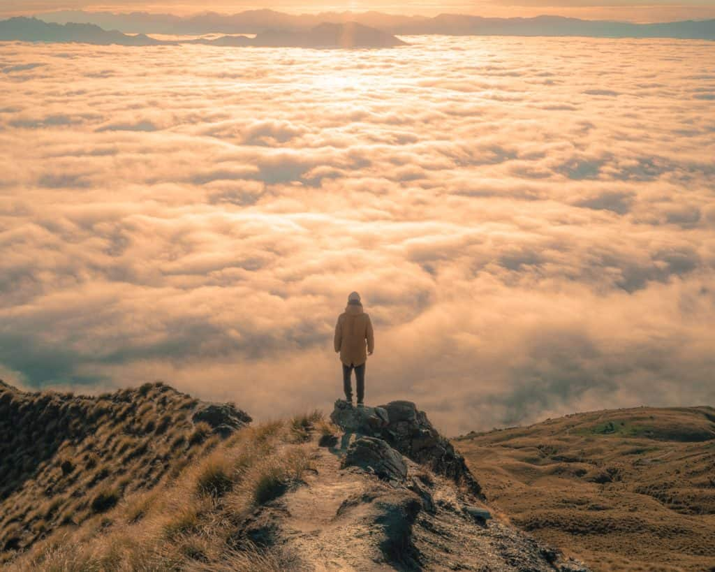 Person standing on a mountain looking out over the clouds