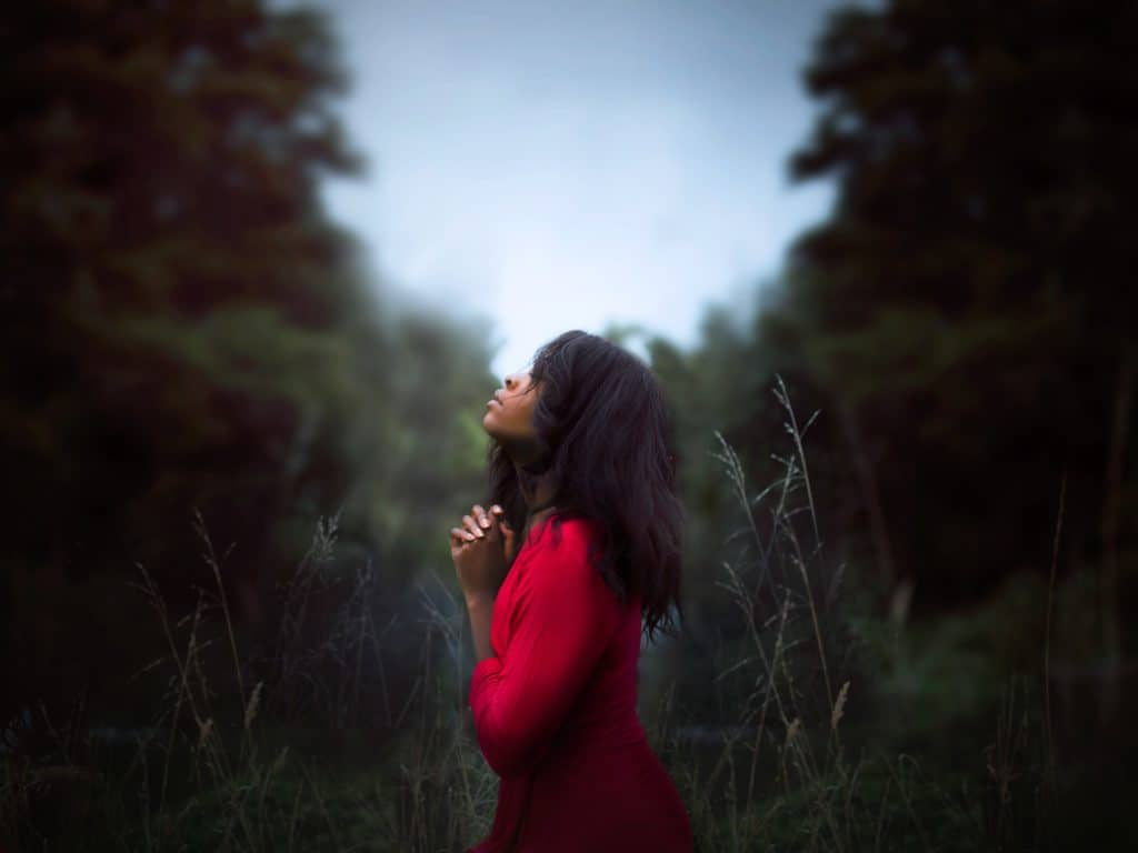 Beautiful woman standing in a forest with her head raised and praying