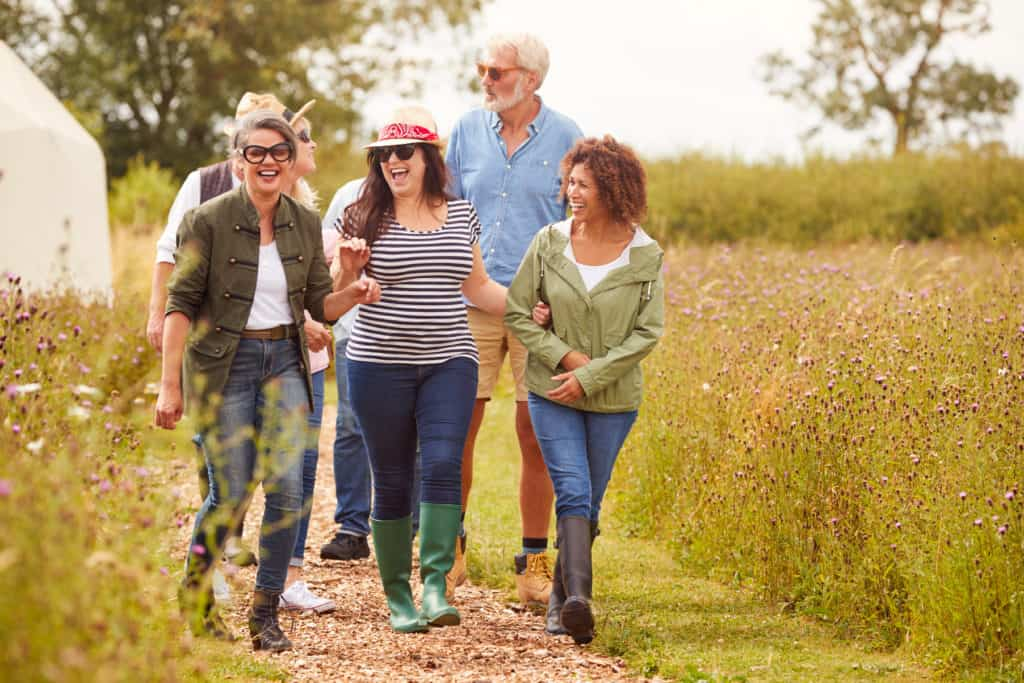 Group Of Mature Friends Walking Along Path Through Yurt Campsite