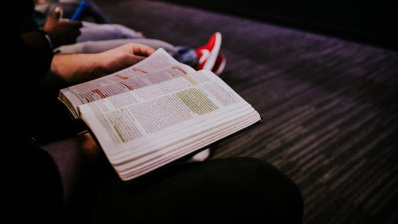 Person sitting at church reading a highlighted Bible
