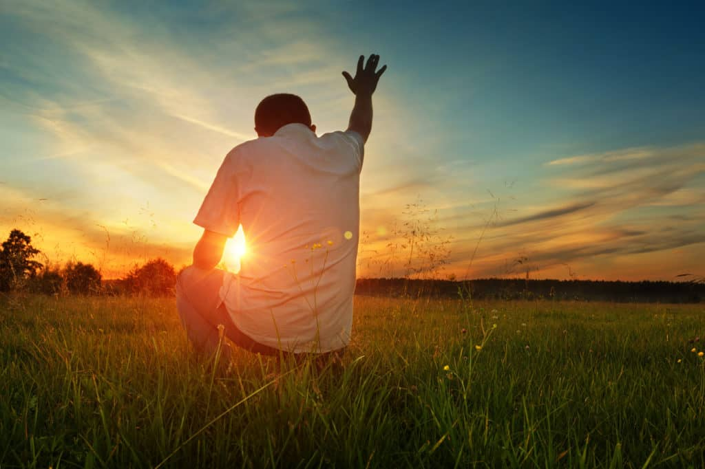 Man prays to God at sunset with hand outstretched