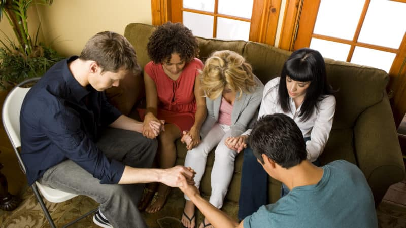 A group of people praying and holding hands on the Sabbath