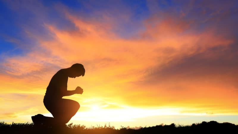 silhouette of man kneeling and praying during beautiful sunset at the close of the Sabbath