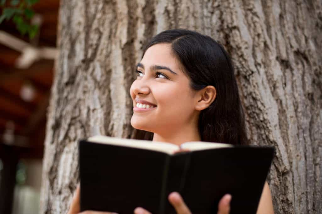 A beautiful young lady with a Bible in hand in the park in this horizontal shot.