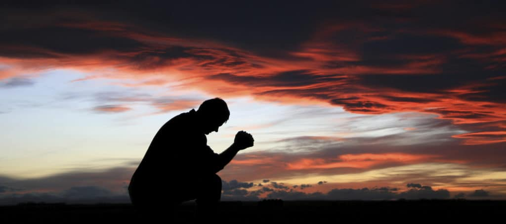Silhouette of man kneeling and praying at sunset