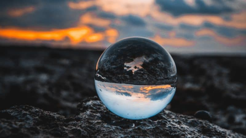 Glass orb sitting on a rock at sunset