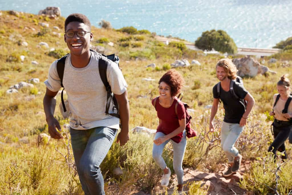 Millennial African American man leading a hike by the coast with friends, smiling to camera