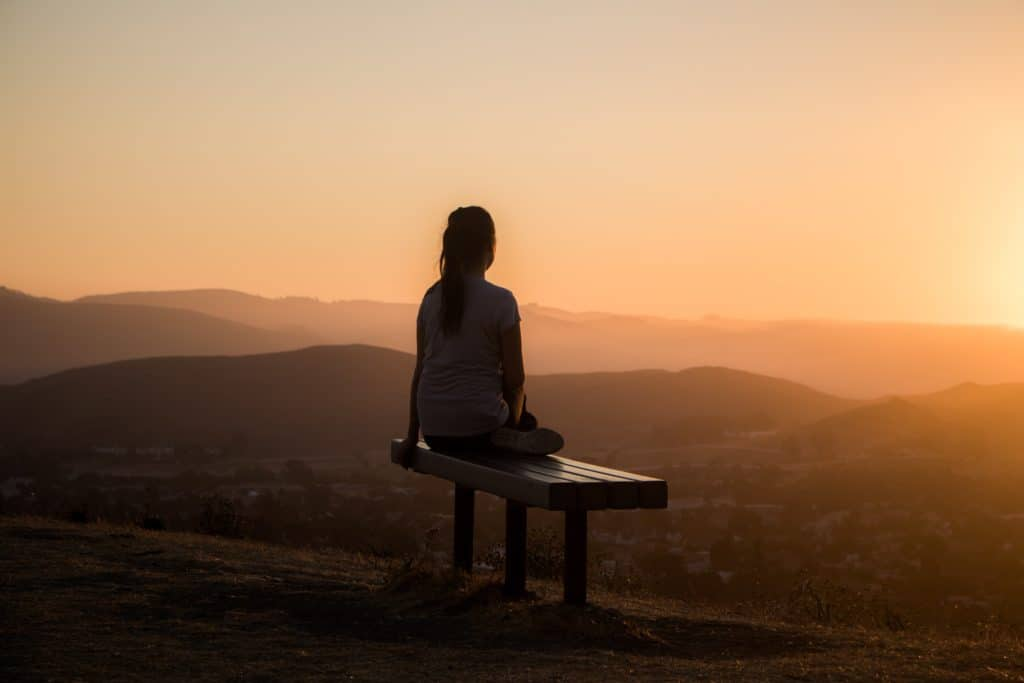 Woman sitting on a bench looking at hills at sunset